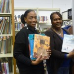 Derrian Jones and Priscilla Barbee display some of the books available in library outreach services.