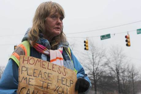 Tammy stands illegally with her sign. The new ordinance prohibits standing on the side of a road without a sidewalk. (Staff photo by Caitlin Owens)
