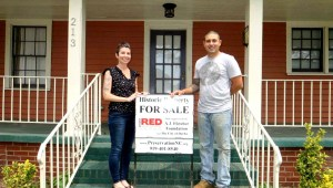 New homeowners Caryn Braunstein and Emmanuel Rittner stand in front of their new home on 213 S. Driver St. Photo by: Preservation North Carolina