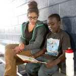 Teacher Regina Diaz and student Mose Cannon read a book as Matthew Graves retrieves a basketball.
