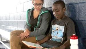Teacher Regina Diaz and student Mose Cannon read a book as Matthew Graves retrieves a basketball.