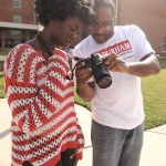 During an instructional photo shoot for The Durham VOICE, mentor Carlton Koonce helps Natasha Graham with her shooting techniques. As a Partners for Youth Opportunity student, Graham earns an hourly wage for her help in producing the Durham VOICE.