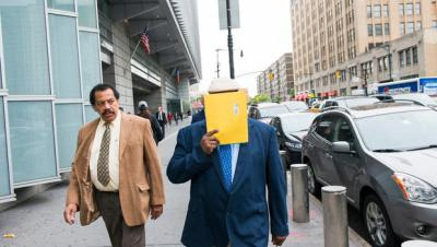 Jorge Hernaiz, covering his face, leaves the Bronx County Hall of Justice after a court appearance in June 2015.  ADRIAN FUSSELL/RIVERDALE PRESS