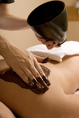 masseuse pouring chocolate on back