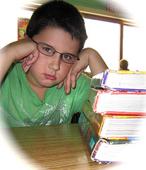 boy frowning near pile of school books