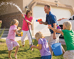 Mom, Dad, and 3 kids having water fight