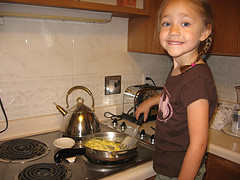 girl at stove cooking eggs