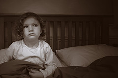child sitting in bedroom looking fearful of dark