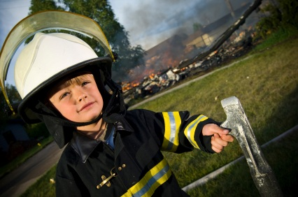young boy wearing firefighter gear in front of burned out building