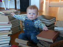 small boy sitting on piles of books