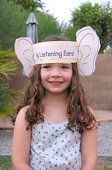 "girl with large paper ears titled ""listening ears"""