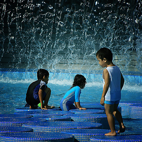kids playing in pool with fountain
