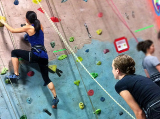 girl climbing rock wall while boy watches and holds ropes