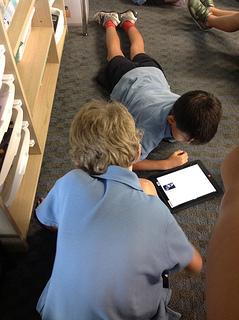 boys lying on floor looking at ipad together