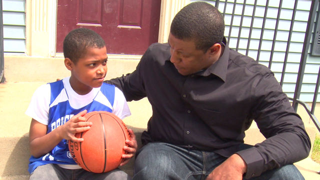 father talking to son holding basketball