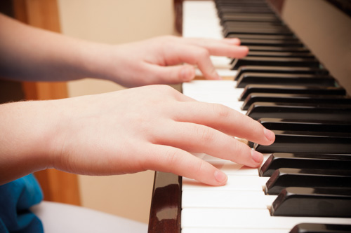 child's hand playing on piano