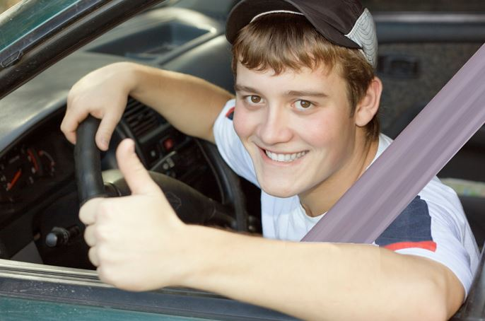 teen boy in driver's seat giving thumbs up sign