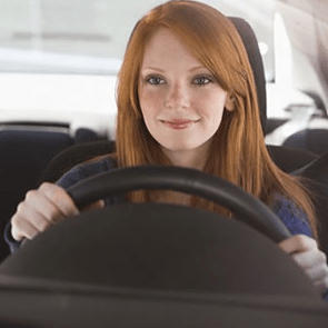 teen girl smiling while sitting in driver's seat