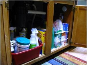 cupboard under sink filled with cleaning supplies