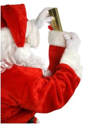 Santa Claus putting gift into stocking