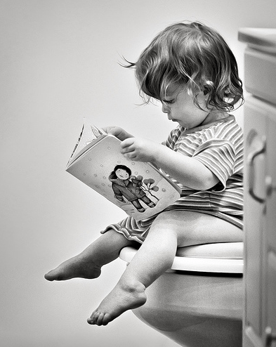 toddler girl sitting on toilet reading book