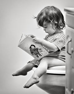 toddler girl sitting on toilet reading book