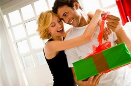 wife hugging husband as he smiles at gift box