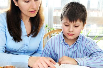 mom and son doing schoolwork at table