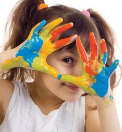smiling girl holding up paint-covered hands