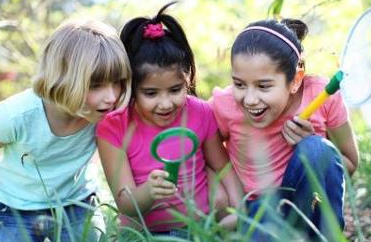 3 girls looking through magnifying glass at grass