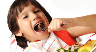 smiling child eating a bite of food