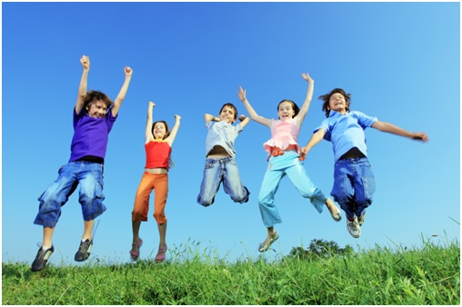 5 kids jumping joyfully in green grass with blue sky
