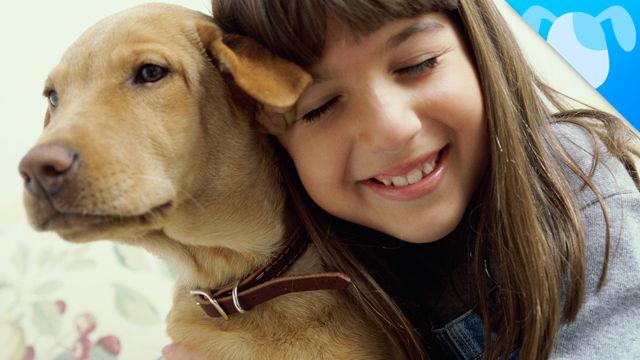 girl smiling and hugging dog