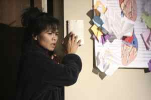 Tess Lina as troubled origami expert Ilana (Tess Lina).