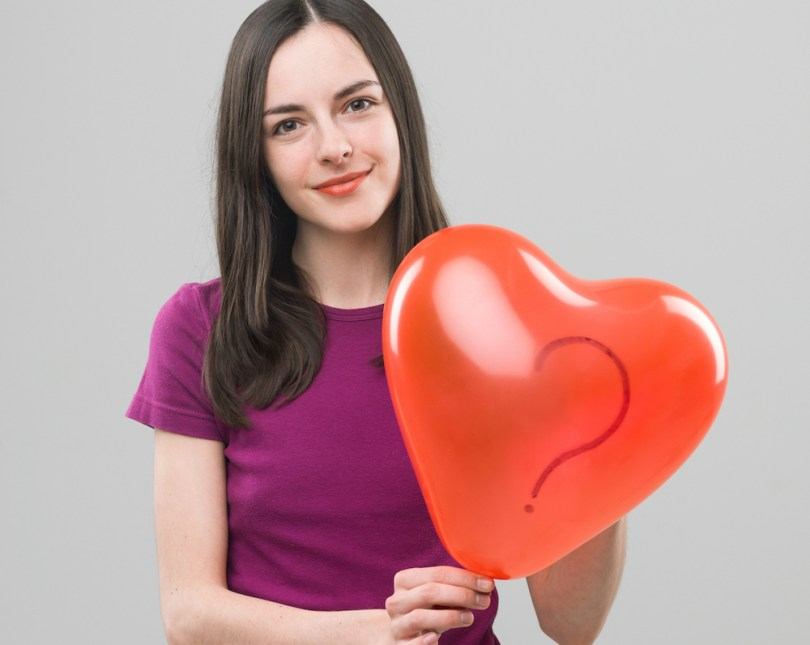 young caucasian woman holding heart shaped balloon with question mark and smiling. copy space available