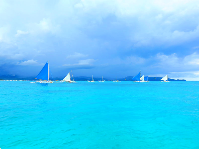 Turquoise sea with paraws in distance