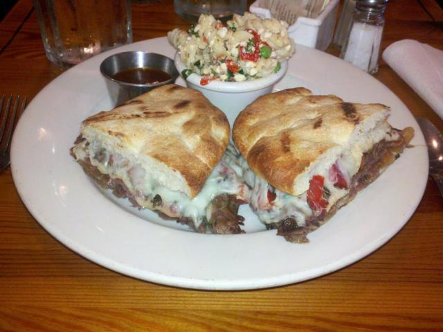 hoisin braised short rib panini with caramelized onion, provolone cheese and tomato cruda on house flatbread with a side of sweet and spicy steak sauce