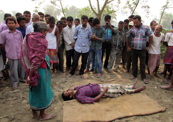 In this photograph taken on March 25, 2015, neighbours and family members of deceased farmer Nityagopal Barman (43) stand around his body after he commited suicide at his home in Dhupguri village, in the Jalpaiguri district of West Bengal state.  Family members found the body of Barman, who commited suicide, hanging on a tree at his home.  Farmers in different parts of Bengal committed suicide after being unable to repay his agricultural loans despite a bumper crop, taking the toll in the state to eight.  AFP PHOTO / AFP / STR