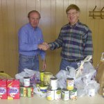 Macolm O'neal, President of the Johnston Sertoma Club, presents to Doc Watson, a Johnston Food Bank volunteer, hundreds of canned goods to help the Food Bank. Photo was taken at the February 11 meeting of Sertoma.