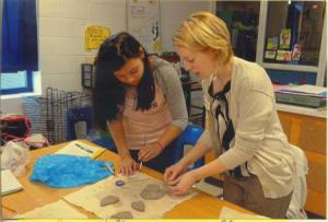 Ms. Katherine Vartanian (far left), art teacher at JET Middle School, assists her students in their clay-making.