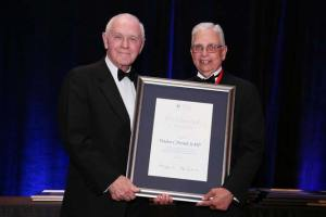 Dr. Derrick left) is presented the Presidential Citation at recent AUA meeting.
