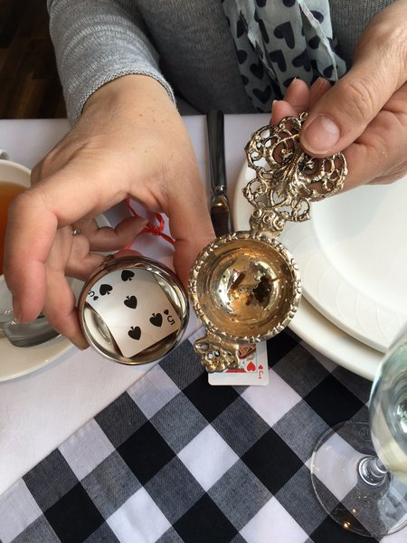 Miniature playing cards in the tea strainer!