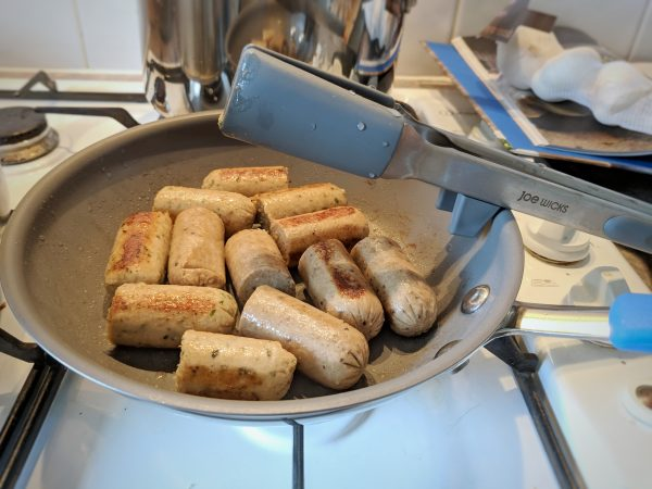 Clever-clogs non-stick suacepan frying sausages for sausage and red wine casserole. Note the sensible tongs on the side.