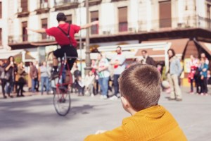 Boy watching someone perform on a unicycle