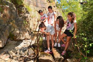 Un grupo de niños ponferradino bebe de la manguera por la que manan las aguas. / QUINITO
