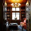 Chandelier in eight globes lights this jewel box of a media room / library.
