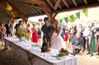 english countryside barn wedding bride groom cut cake
