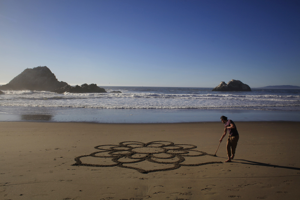 Andres Amador works on a mandala shaped sand mural, he calls an Earthscape, at Ocean Beach in San Francisco, Calif.