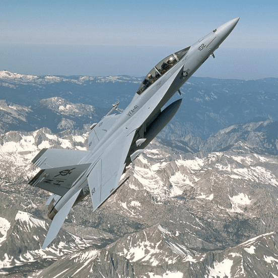 F/A-18F Super Hornet at high angle of attack over a snowy mountain range.