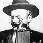 Still from Orson Welles's Citizen Kane, showing Charles Foster Kane giving a campaign speech in front of a massive likeness of his own face